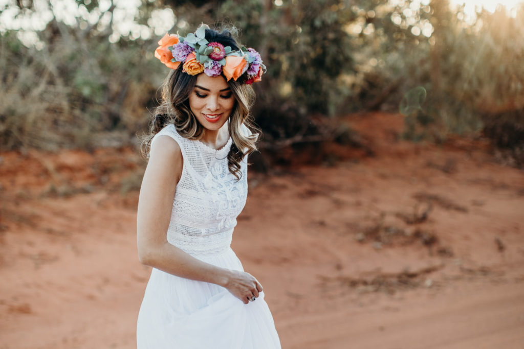 young women wearing a large flower crown and a Kimberley bride outfit, twirling her Zolotas Australia dress