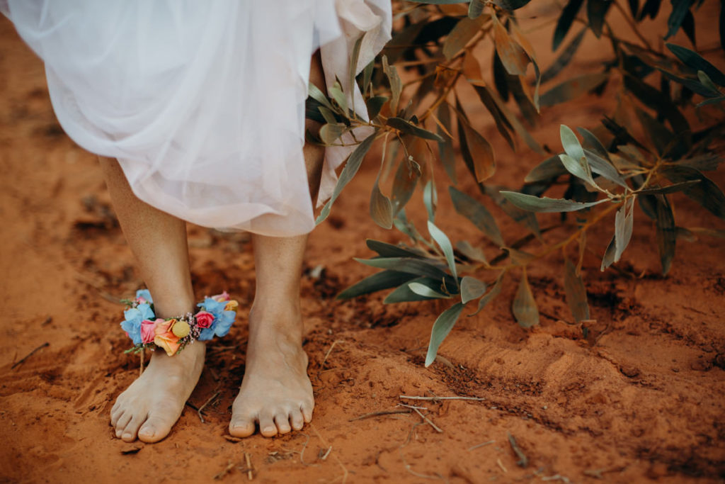 barefoot feet in red Kimberley dirt with a flower anklet