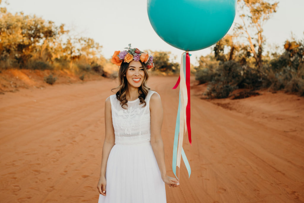 young woman standing on red dirt road in the Kimberley wearing a Zolotas Australia dress and a flower crown, and holding a big balloon