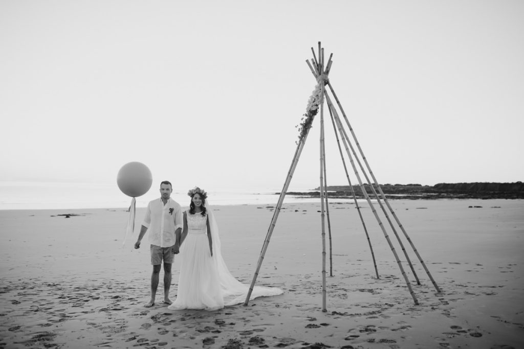 wedding couple standing next to a bamboo tepee on the beach in Broome