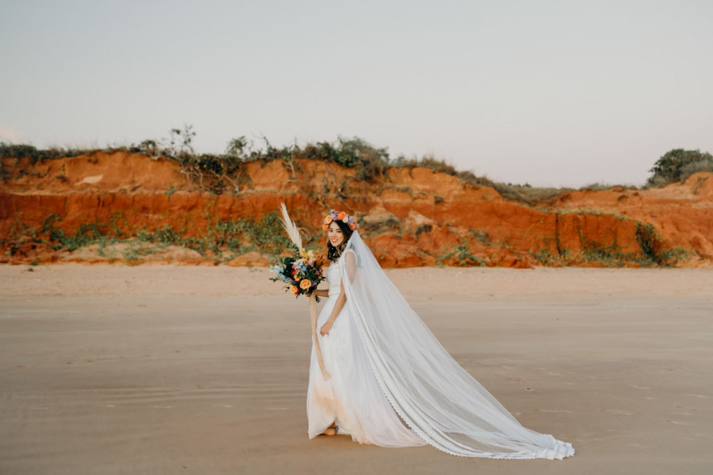 Kimberley bride in Zoloatas Australia dress and long veil walking on beach with red cliffs