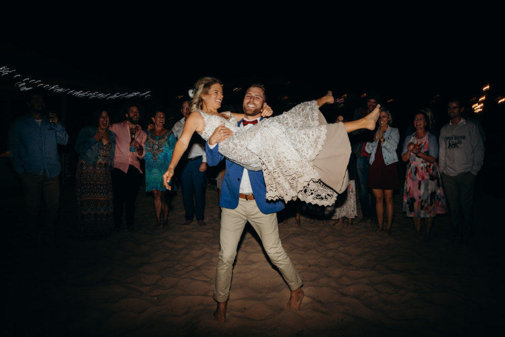 groom lifts up his bride on the sandy beach dance floor at their Eco Beach Resort wedding