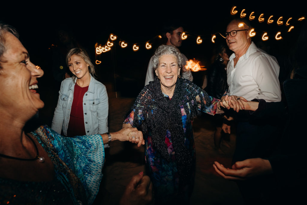 group of people dancing at Eco Beach Resort wedding with old women smiling