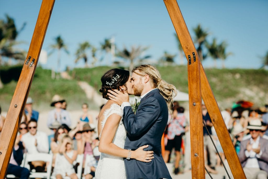 bride and groom kiss at their Cable Beach ceremony with their guests looking on