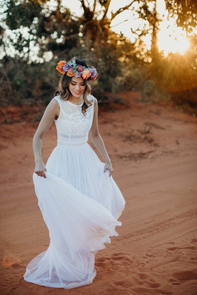 bride is white lace dress and flower crown is spinning her dress on a dirt road in Broome neear Gantheaume Point