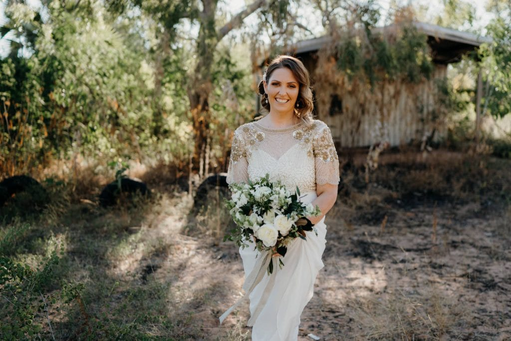 bride in white and golden dress with flower bouquet in front of old shack in bushland near Cape Leveque