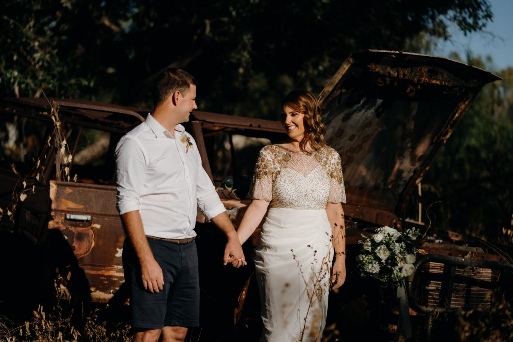 Cape Leveque elopement couple standing in front of old car wreck holding hands