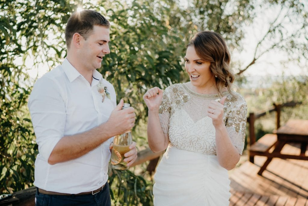 groom pops the Champagne after Cape Leveque elopement ceremony with bride cheering him on