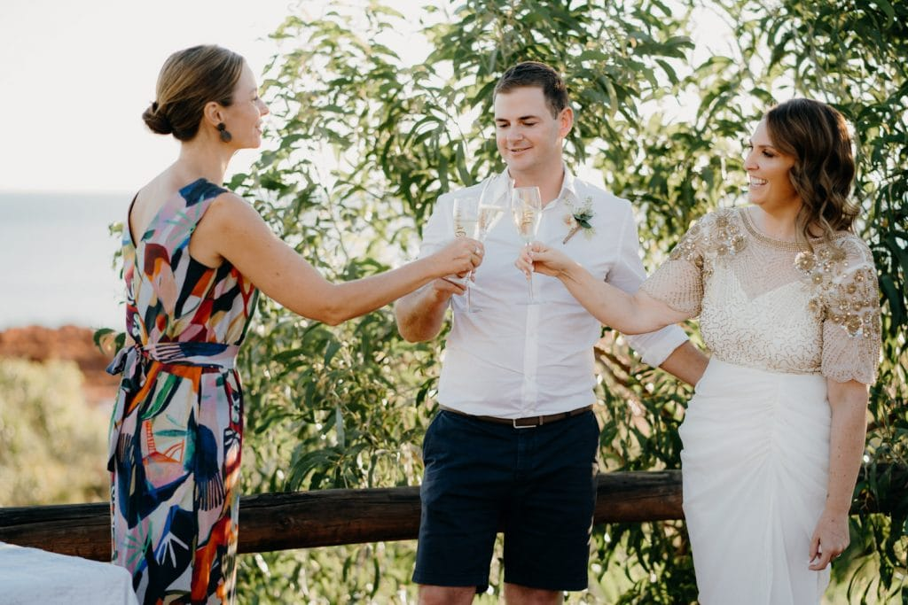 wedding couple and celebrant celebrate by cheering with champagne at Cape Leveque elopement wedding