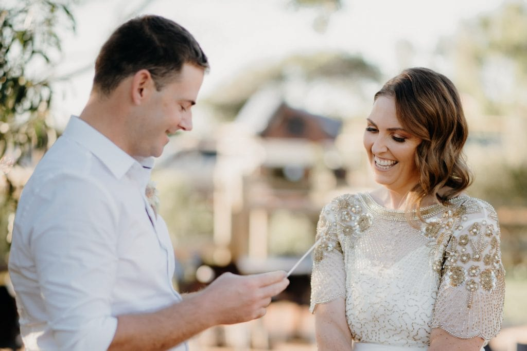 groom in white short reads vows of card to his new wife