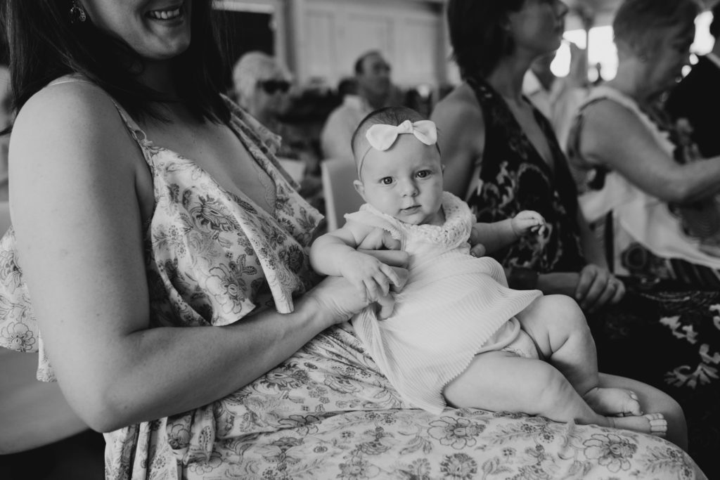 Baby sitting on her mothers lap at Broome church wedding Julia Rau Photography