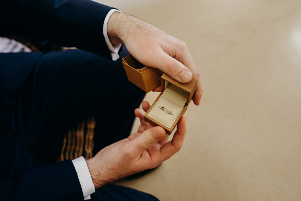 close up of wedding ring in box held by a man in suit