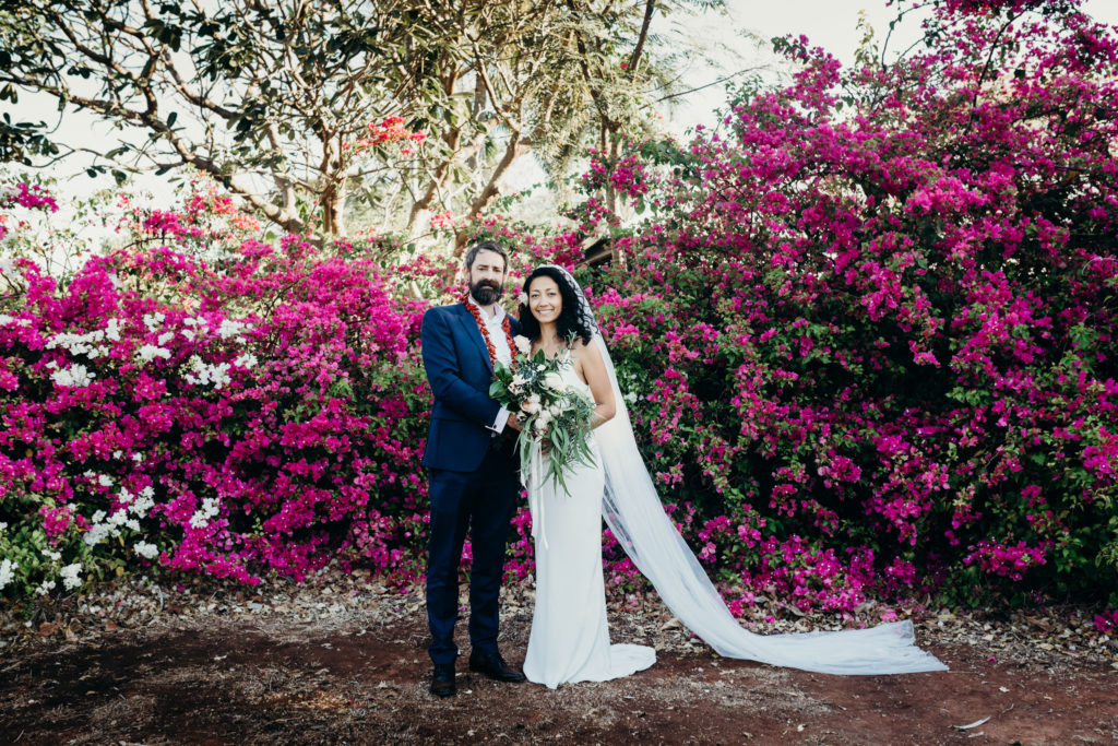 bride and groom stand in front of a larhe Bougainvillea bush behind Uniting Church in Broome