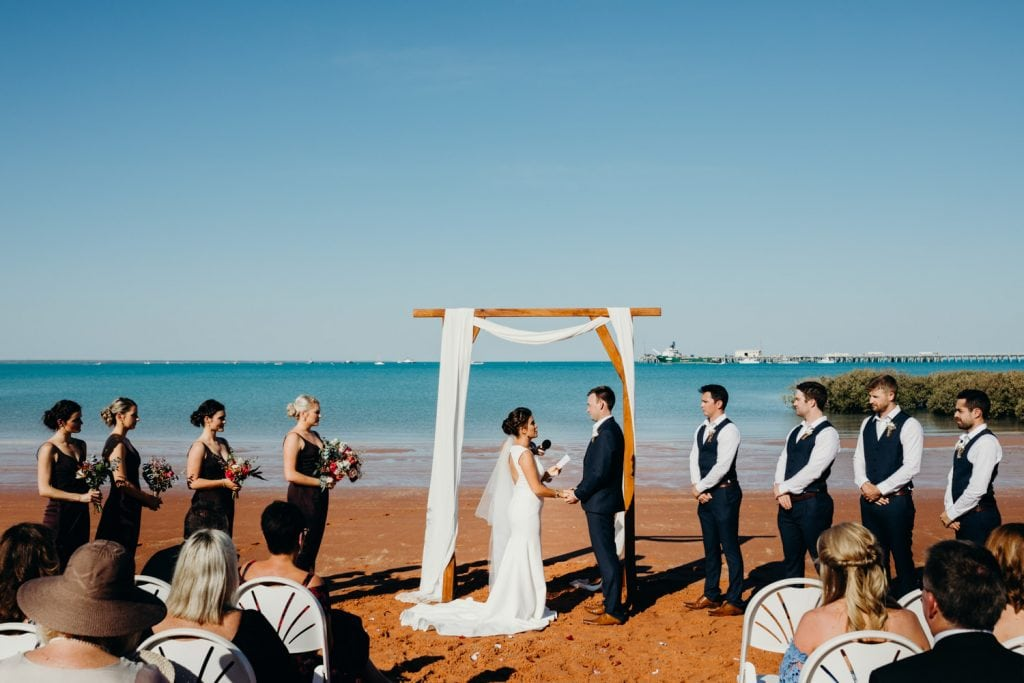 Wedding ceremony at Broome Hovercraft Base with couple standing under a wooden arbour