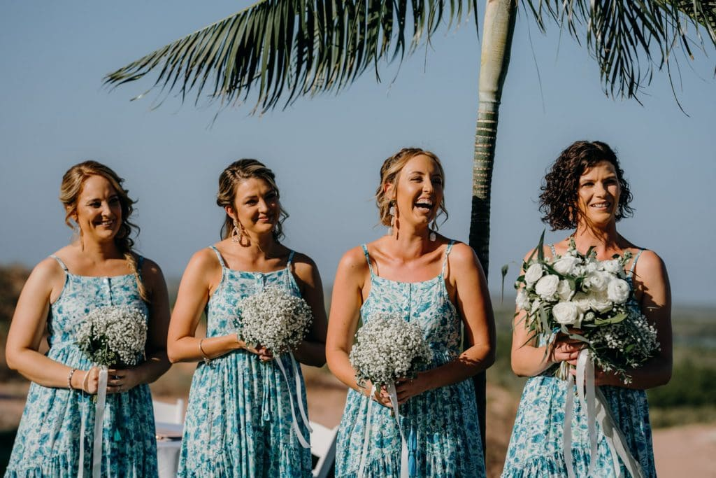 four bridesmaids in blue summer dresses and flower bouquets standing in a line at Mangrove Hotel wedding