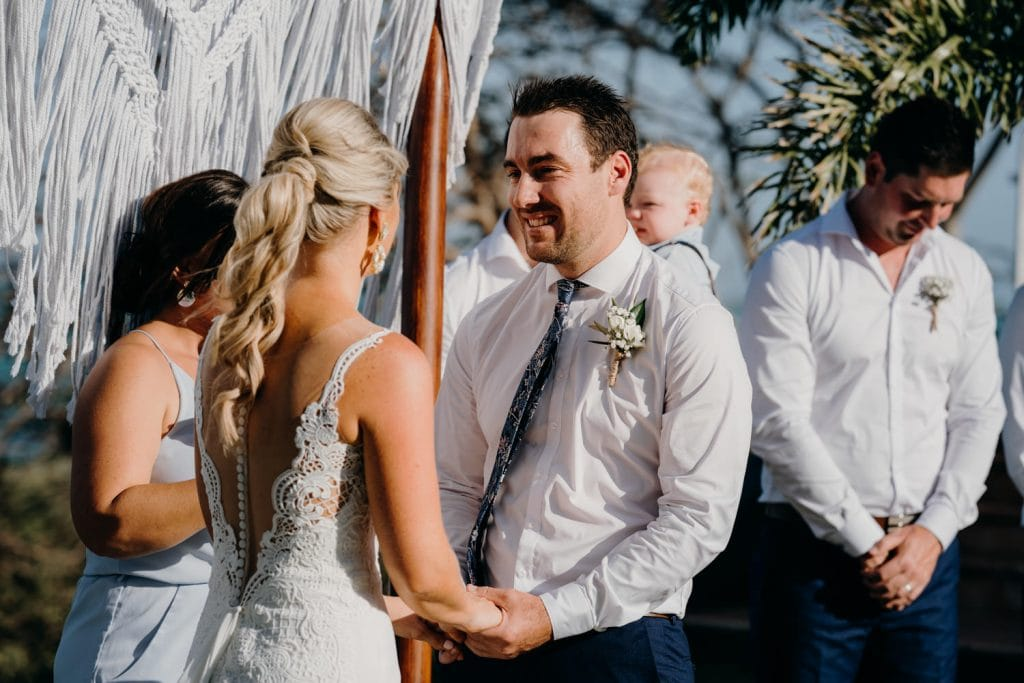 bride and groom holding hands during their ceremony with Elle Saunders as their marriage celebrant