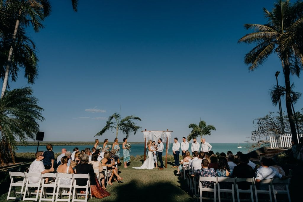 wide shot of wedding ceremony at the Mangrove Hotel in Broome with ocean views and palm trees