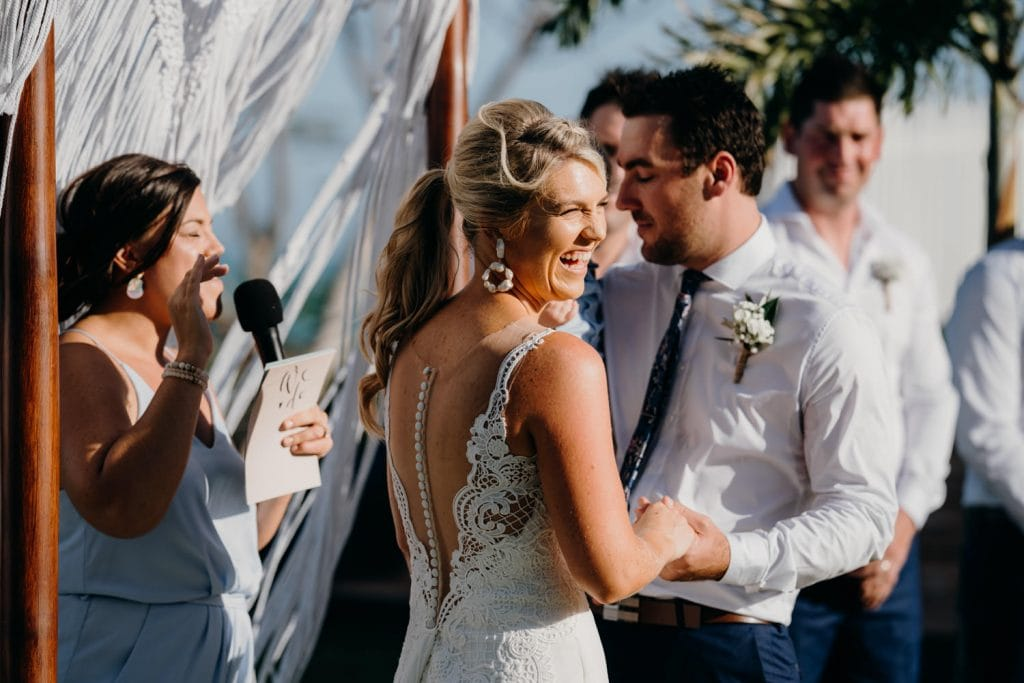 laughing bride holding her groom's hands during outdoor ceremony in Broome