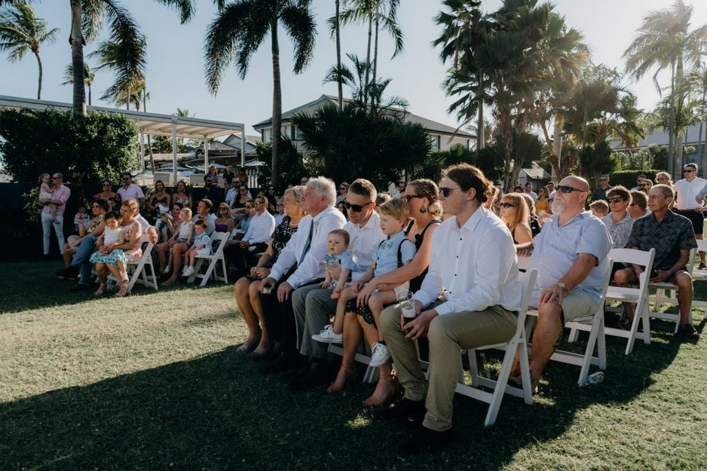 wedding guests seated on rows of chairs on green lawn at Mangrove Hotel