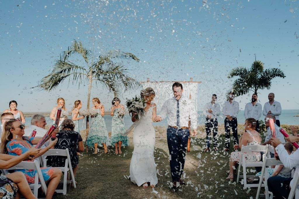 wedding couple walks down the aisle at Mangrove Hotel wedding with confetti canons going off