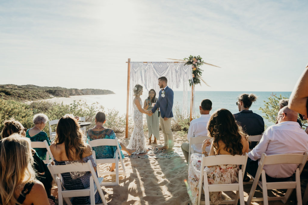 guests are seated on chair watching wedding ceremony with ocean as backdrop