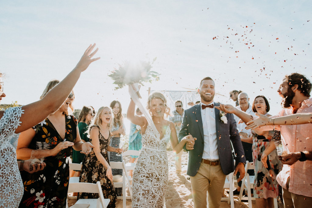 bride and groom walk down the aisle as married couple with friends and family throwing confetti at Eco Beach Resort wedding