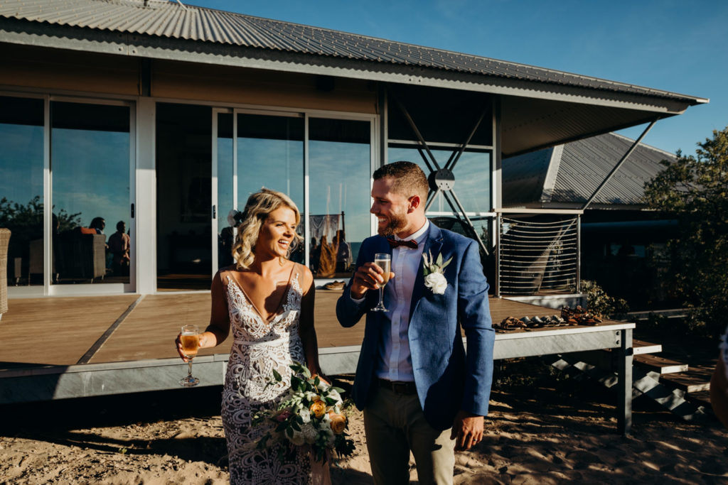freshly married couple at their Eco Beach Resort wedding with glasses of champagne in their hands