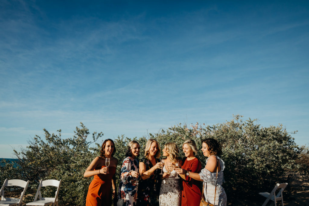 group of women are cheering with glasses of champagne at Eco Beach Resort wedding