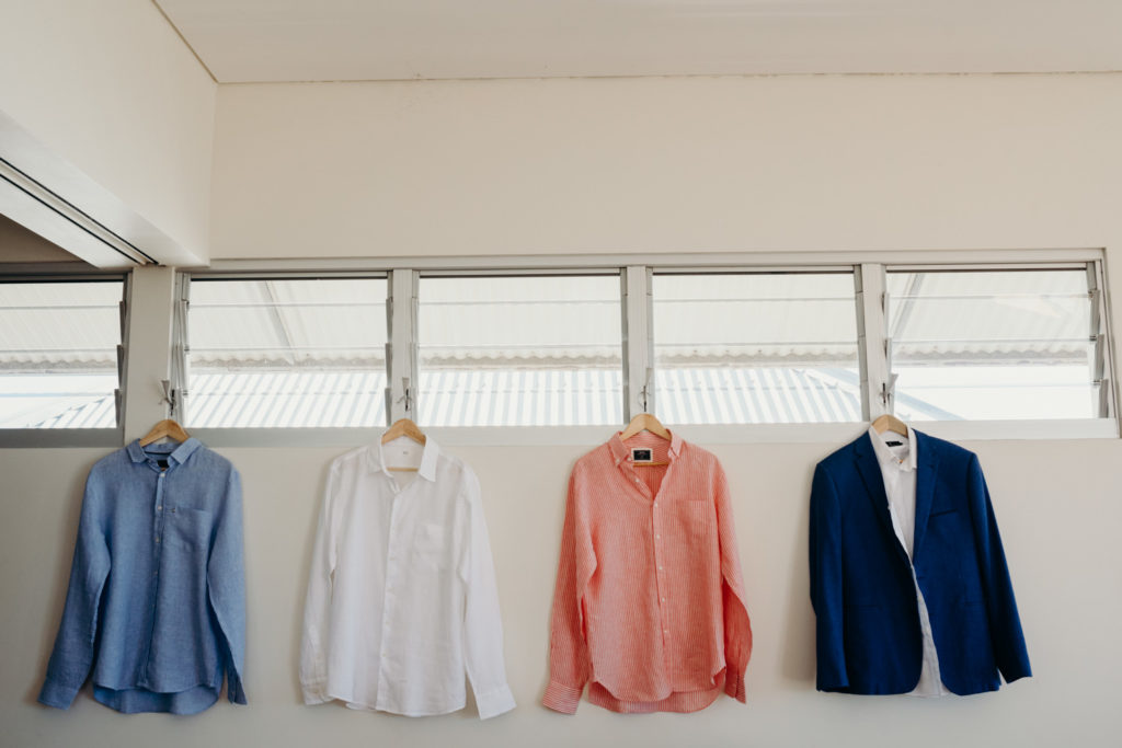 shirts in different colours hanging on hangers in villa at Eco Beach Resort wedding