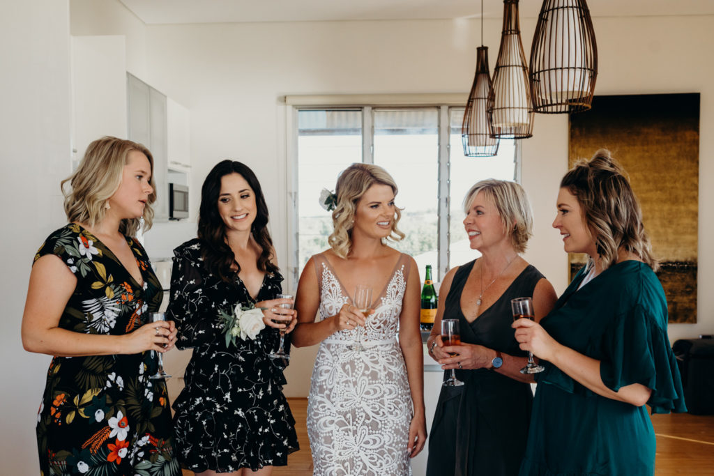five women standing in half circle in hotel room with champagne glasses