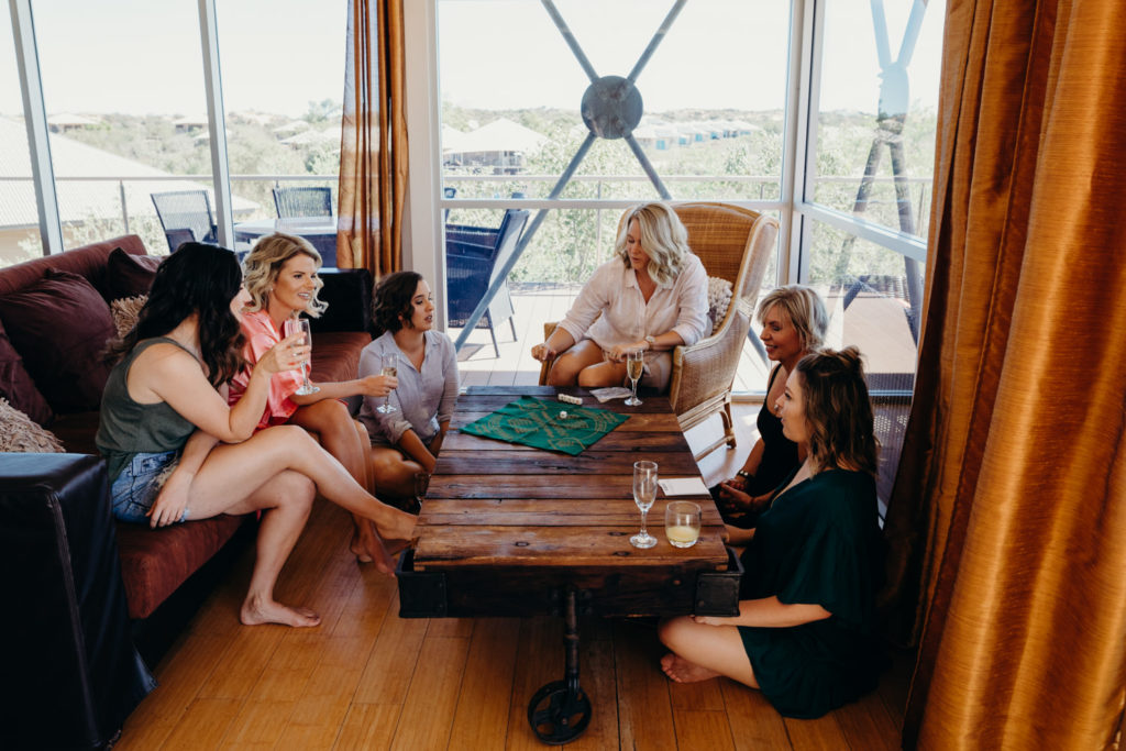group of women sits around table playing board game at Eco Beach Resort wedding
