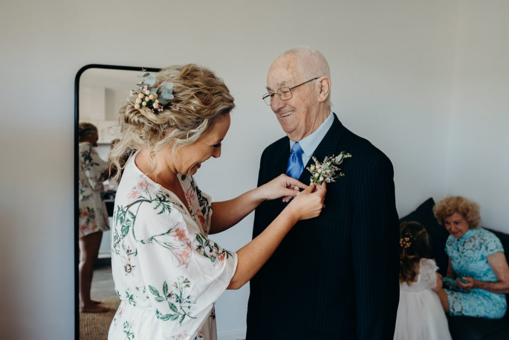 Bride fixing button hole on her grandfather's jacket