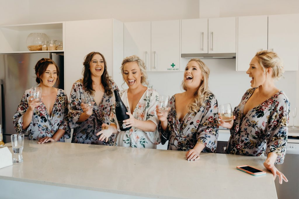 bride and her bridesmaids popping open a bottle of champagne for Mangrove Hotel wedding