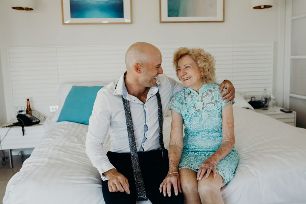 Broome groom with grandmother sitting on bed in hotel room at Mangrove Hotel wedding