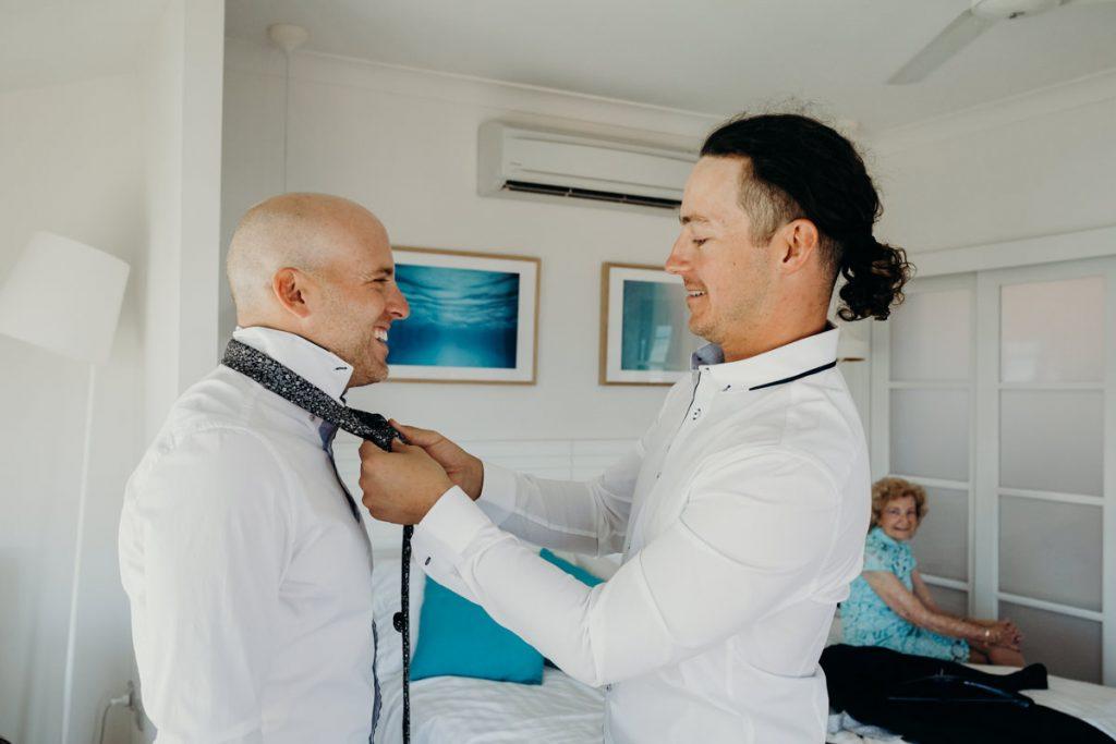 best man is tying tie around groom's neck at Mangrove Hotel in Broome