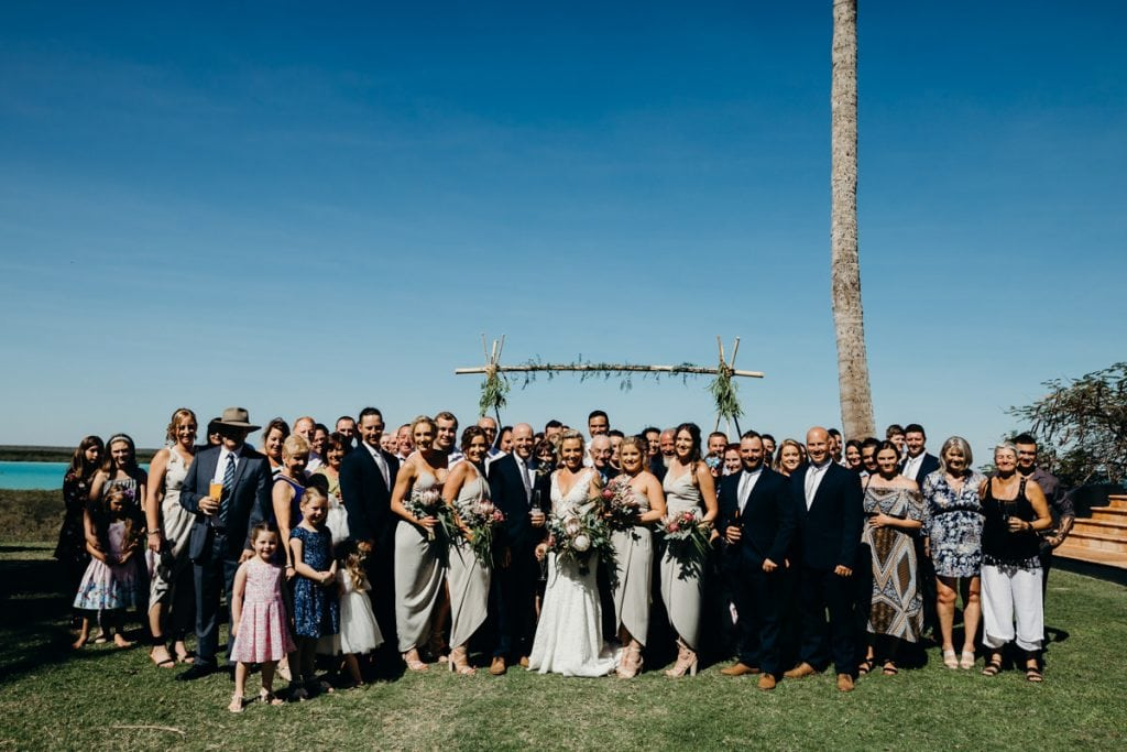 group photo at wedding with arbour and palm tree in the background