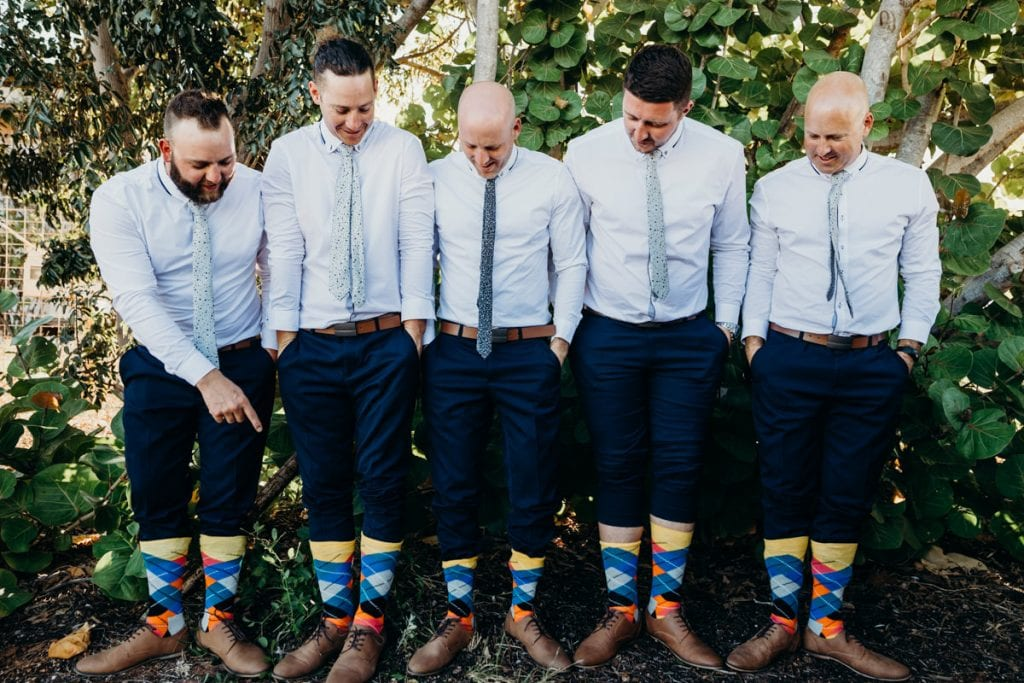 Groomsman pointing at colourful happy socks on Broome wedding day