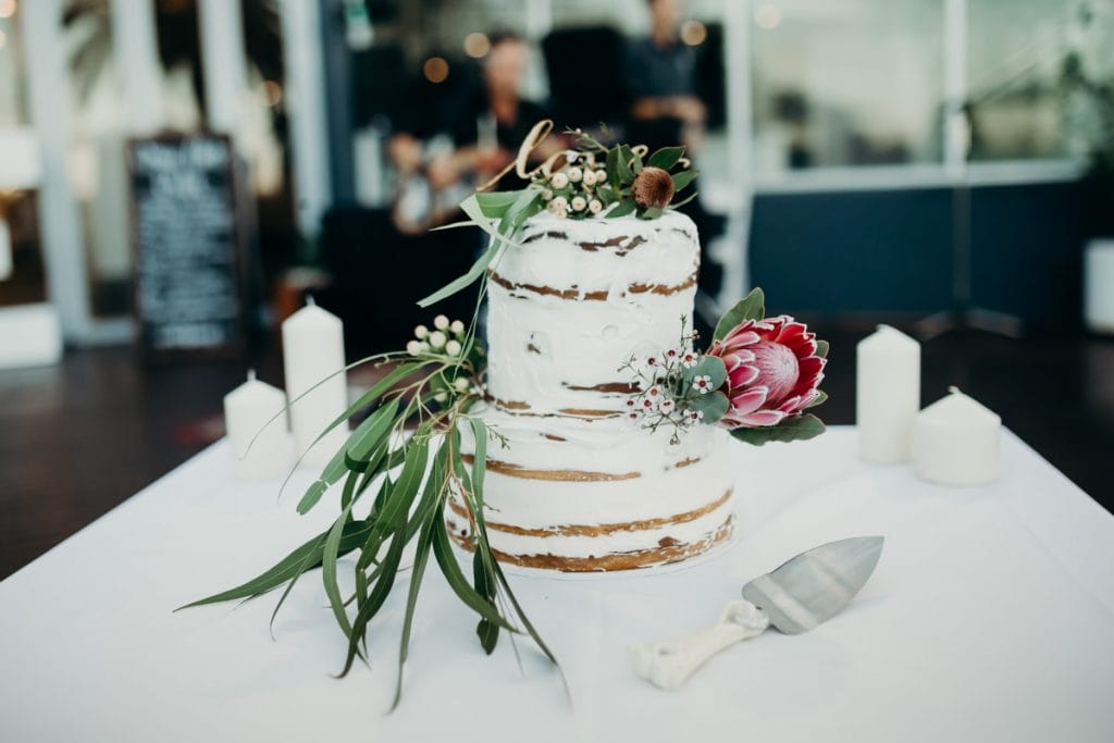 wedding cake with Broome Florist flower and love topper