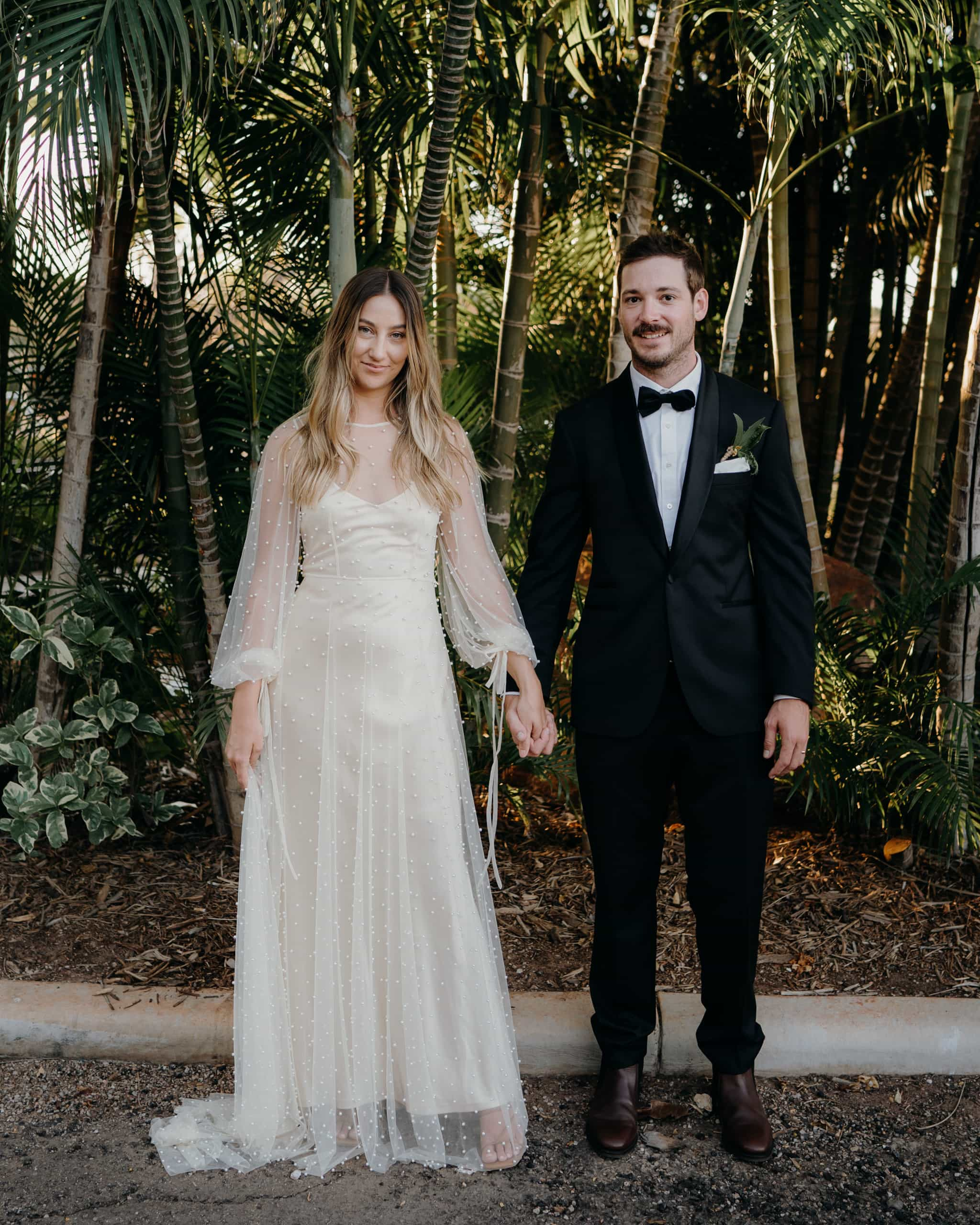 wedding couple standing next to each other and holding hands