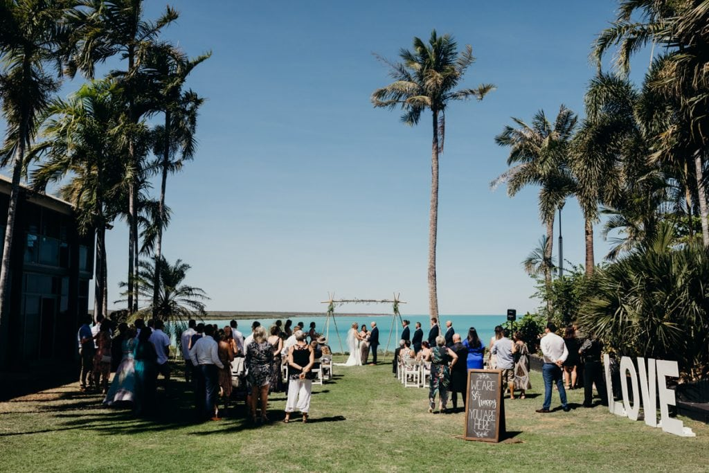 getting married in Broome with palm trees and blue ocean as a backdrop at the Mangrove Hotel