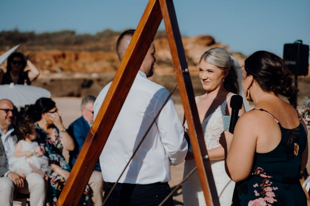 bride and groom facing each other during relaxed beach wedding at Entrance Point with celebrant holding microphone