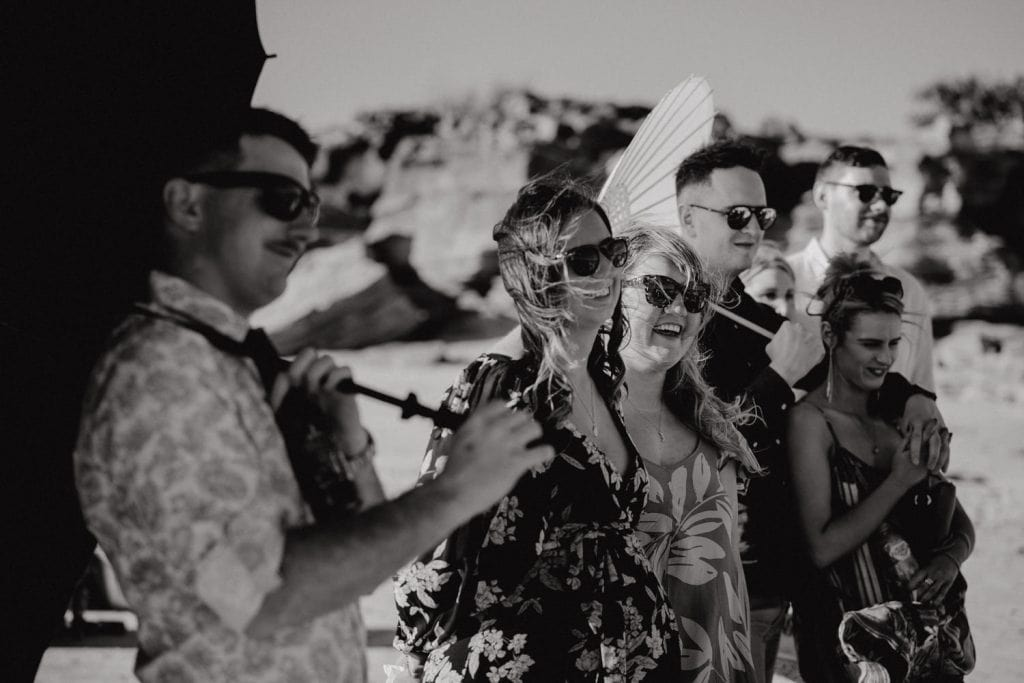 black and white photo of guests at beach wedding with hair flying in the wind and sun parasols
