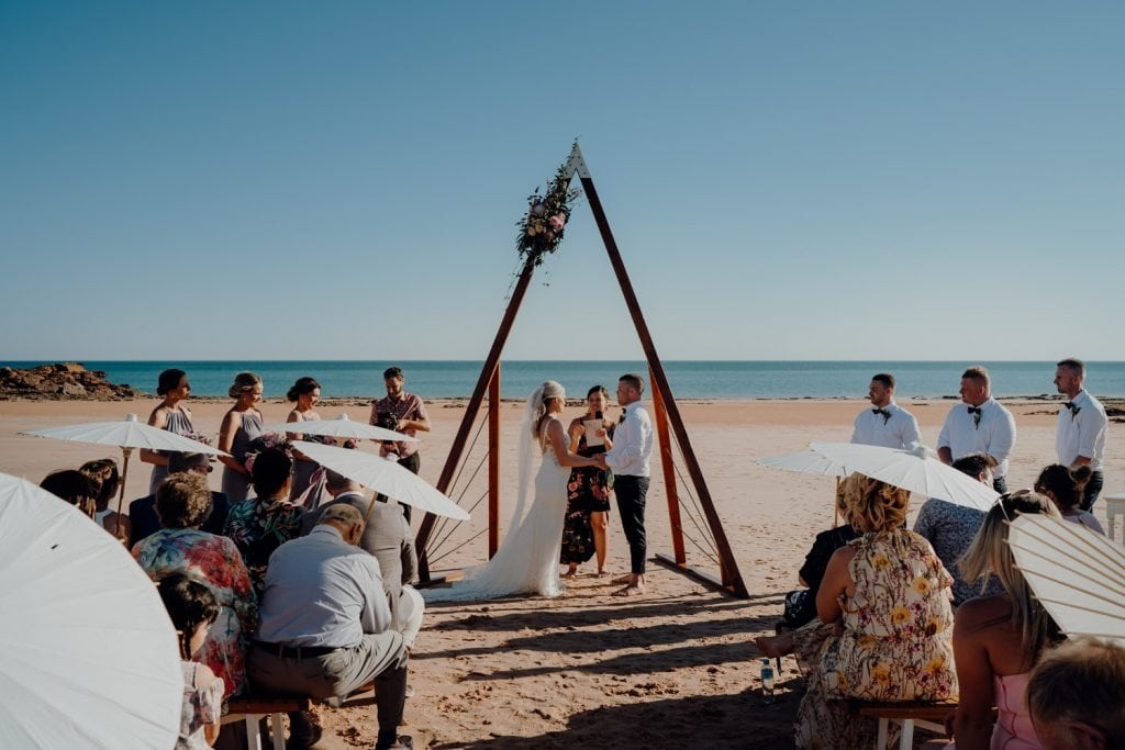 wedding ceremony set up with triangle arbour and ocean as backdrop