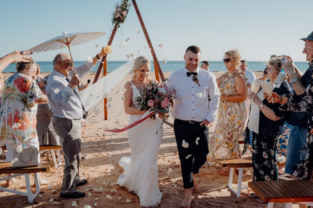 bride and groom walking down the sandy aisle at their relaxed beach wedding with flowers being thrown at them