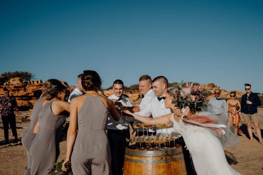 bridal party cheers with champagne to celebrant the wedding