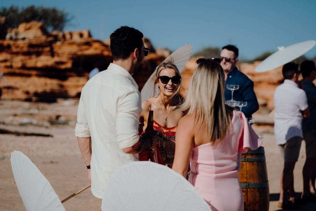 three people having an engaging conversation at beach wedding in Broome