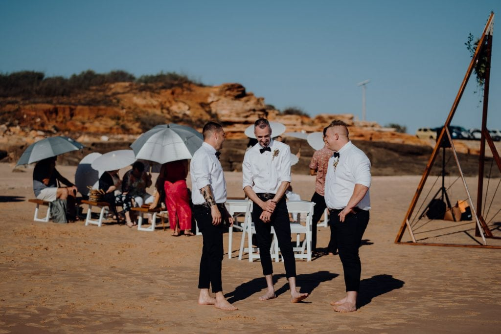 three young men in black pants and white shirts at beach wedding at Entrance Point