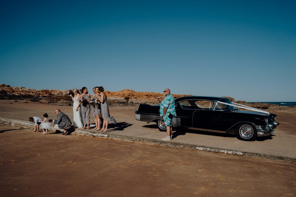 bridal party standing next to a black Cadillac at Entrance Point beach in Broome