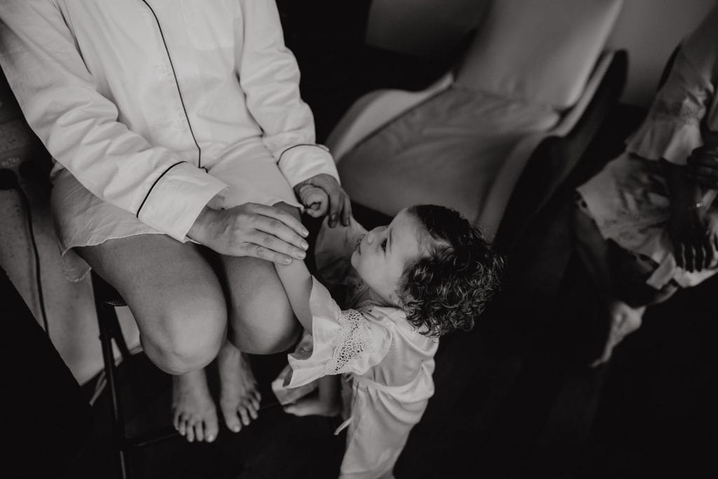 black and white photo of bride holding the hands of her little daughter during the getting ready