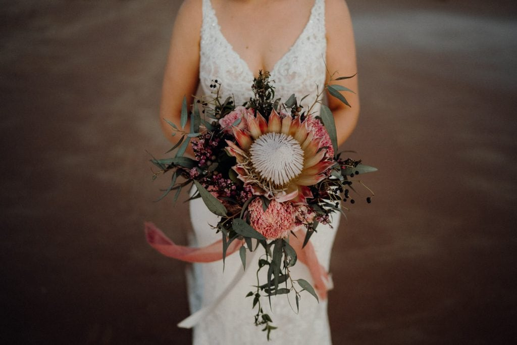 close up of flower bouquet with large protea in the middle held up by bride and white dress